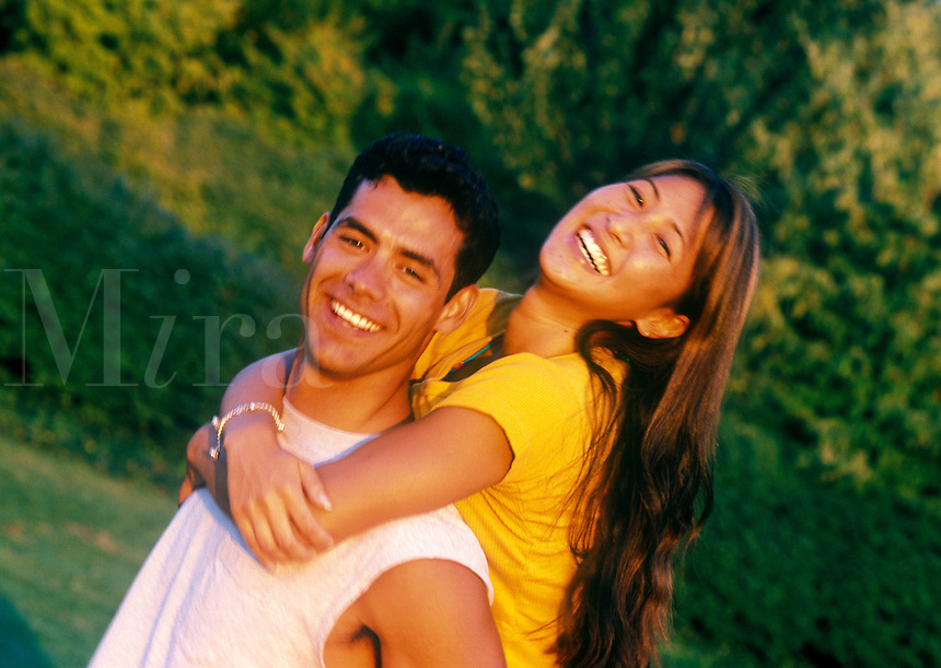 Young man gives his girlfriend a piggyback ride.