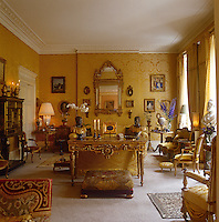 This grand drawing room is formally furnished with walls clad in yellow-gold silk damask and soft furnishings to match
