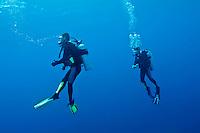 Two scuba divers searching for a giant manta ray near the Kaafu Atoll, Maldive Islands.