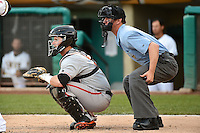 Andrew Susac (5) of the Fresno Grizzlies behind the plate with home plate umpire Scott Mahoney as the Grizzlies battled the Salt Lake Bees in Pacific Coast League action at Smith's Ballpark on April 9, 2014 in Salt Lake City, Utah.  (Stephen Smith/Four Seam Images)
