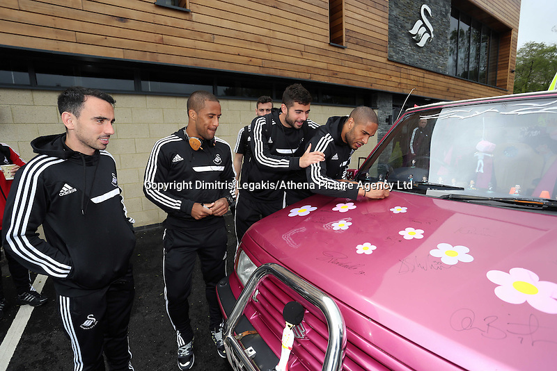 """Pictured L-R: Players Leon Britton, Wayne Routledge, Jordi Amat and Ashley Williams sign the Suzuki Samurai at the Landore Training Ground. Saturday 10 May 2014<br /> Re: Leigh Evans of Leigh Enterprise Tyres is the new owner of """"the pink Ferrari"""", an old Suzuki Samurai 4x4 car used by Swansea City FC players during the last season."""