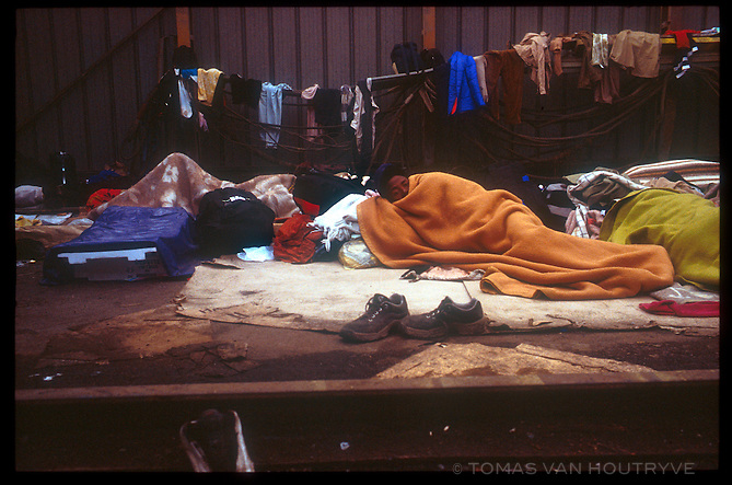 A migrant from Sudan sleeps with other refugees in an abandoned warehouse in Calais, France on Oct. 23, 2003. French police regularly empty the warehouse and detain refugees without papers, but they are soon released and eventually return to the same spot.