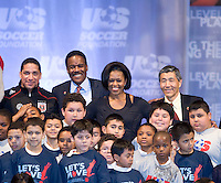 First Lady Michelle Obama poses with the assembled crowd, including US Soccer President and CEO Ed Foster-Simeon and DC United owner Will Chang during a US Soccer Foundation clinic held at City Center in Washington, DC.