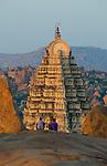 Tourists enjoying the view from Hemakuta Hill onto Virupaksha Temple at sunset in Hampi, Karnataka, India.