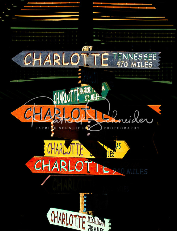 """Photo of the iconic Charlotte signs statue/public art located on The Green in Uptown Charlotte. The Green, actually the top level of an underground parking garage, is a tiered outdoor space with a lawn, lush gardens, interactive fountains and abundant public art. Contemporary artist Gary Sweeney, based in San Antonio, created the piece named """"Charlotte - The Center of the Known World."""" The signs point to 11 other areas also named Charlotte. The signs point to the approximate direction of the locales they identify and the distance to each. .."""