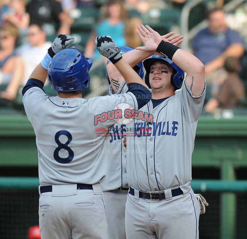 Right fielder Kyle Parker (8) of the Asheville Tourists is congratulated after hitting a home run in a game against the Greenville Drive on May 1, 2011, at Fluor Field at the West End in Greenville, S.C. A former quarterback and outfielder for the Clemson Tigers, Parker was the No. 1 pick of the Colorado Rockies in the 2010 First-Year Player Draft. Photo by Tom Priddy / Four Seam Images