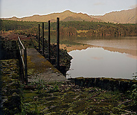 At dawn, a reflection of the mountains in the calm waters of a reservoir, with a foot bridge in the foreground, on Kaua'i.