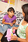 6 year old girl talking with mother at home sitting on bed while mother folds laundry