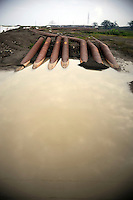 Pipes near a pumping station at the Porong River used to drain the mud. Since May 2006, more than 10,000 people in the Porong subdistrict of Sidoarjo have been displaced by hot mud flowing from a natural gas well that was being drilled by the oil company Lapindo Brantas. The torrent of mud - up to 125,000 cubic metres per day - continued to flow three years later.