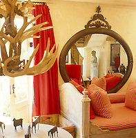 In the living room underneath a chandelier made from antlers a round table displays a collection of tiny carved African animals
