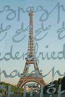 Eiffel Tower, Paris. Shot from the Champs de Mars through the glass of the Wall for Peace.  Wall for Peace script visible in foreground.