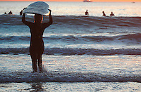 Pacific Beach, San Diego, California, USA:  Monday, January 19 2009.  A  surfer carries her board on her head as she walks out into the line up at the bottom of Loring Street.  The Martin Luther King Jnr Day holiday was marked by warm weather, big surf and a technicolored sunset as much of the rest of the country shivered in the cold.