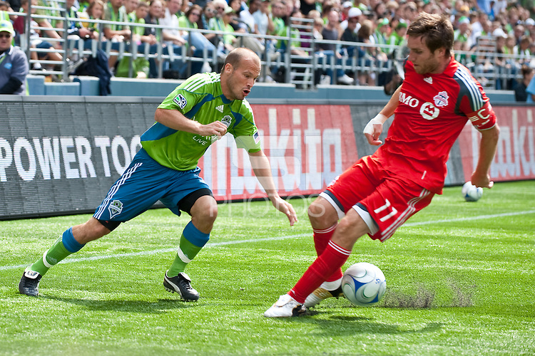 Fredy Ljungberg (L) of the Seattle Sounders drives against Jim Brennan (11) of Toronto FC in the match at the XBox Pitch at Quest Field on August 29, 2009. The Sounders and Toronto played to a 0-0 draw.