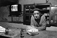 """Spain. Basque Country. Alava province. Lahoz de Valderejo. """"Artalde"""" farmers cooperative. An elderly man wearing a basque beret smokes a cigar while standing alone behind the counter. A beret is a soft, round, flat-crowned cap, usually of woven, hand-knitted wool, crocheted cotton, wool felt, or acrylic fibre. A crockery cabinet and a television on the wall. Two San Miguel beer bottles and a pack of napkins on the wooden bar. Mahou San Miguel is the leading brand in the Spanish beer market. The Basque Country (Euskadi, País Vasco, Pays Basque), officially the Basque Autonomous Community (Euskal Autonomia Erkidegoa, Comunidad Autónoma Vasca, CAV) is an autonomous community in northern Spain. It includes the Basque provinces of Álava, Biscay, and Gipuzkoa. The Basque Country or Basque Autonomous Community was granted the status of nationality within Spain, attributed by the Spanish Constitution of 1978. The autonomous community is based on the Statute of Autonomy of the Basque Country, a foundational legal document providing the framework for the development of the Basque people on Spanish soil. 18.03.92 © 1992 Didier Ruef"""