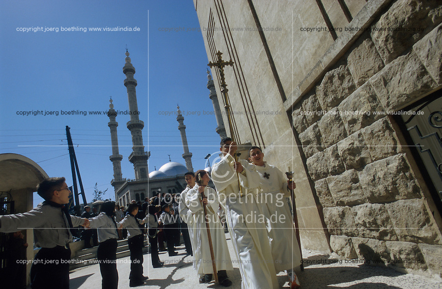 SYRIA Aleppo, chaldean christians at procession at church , background  mosque of Aleppo / SYRIEN Aleppo , Chaldaeische Christen bei Prozession vor einer Kirche, im Hintergrund Moschee von Aleppo