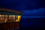A restaurant build above the beach heading the Mediterranean Sea in the blue hour. Orange an blue colors contrasting each other.