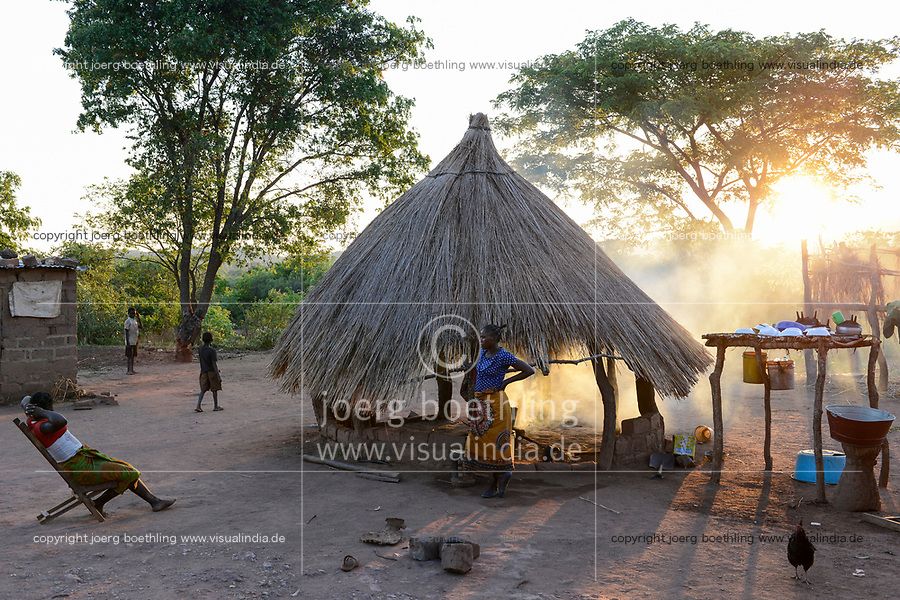 ZAMBIA, Sinazongwe, Tonga tribe, village Siabunkululu, homestead, woman infront of her kitchen hut in the evening / Kueche in Rundhuette, Abendstimmung