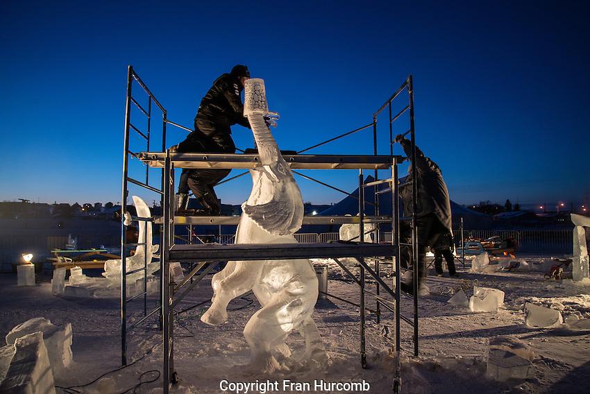 Ice carving taking place at night at Yellowknife's long John Jamboree.