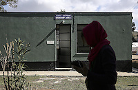 Pictured: A woman walks by the worship area building Friday 26 February 2016<br />Re: Hundreds of refugees have been given temporary shelter at the Stefanakis Army Camp in the Schisto area of Athens, Greece.