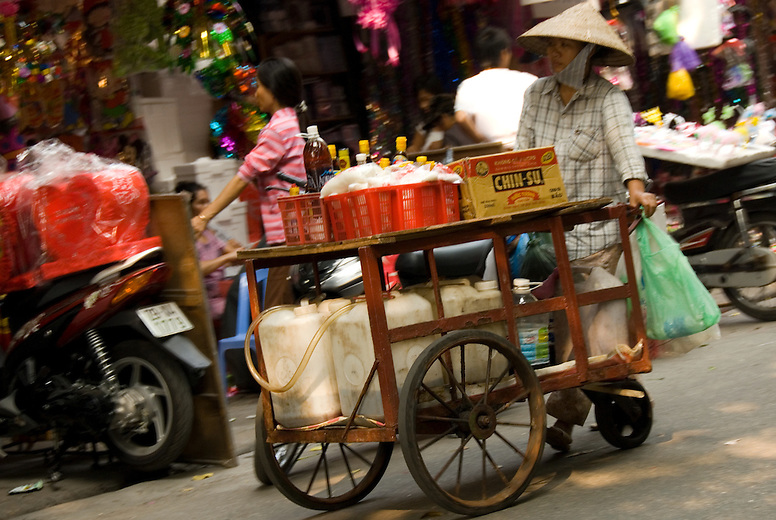A woman in the old quarter in Hanoi, Vietnam sells fuel and oil. The Old Quarter is divided into sections according to the goods sold. One street may have vendors selling household goods and another motorbike supplies or toys.