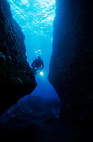 One scuba diver shines an underwater light while swimming through a cave, Marseille, France.