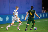 LAKE BUENA VISTA, FL - AUGUST 11: Chris Mueller #9 of Orlando City SC and Jorge Villafana #4 of the Portland Timbers battle for the ball during a game between Orlando City SC and Portland Timbers at ESPN Wide World of Sports on August 11, 2020 in Lake Buena Vista, Florida.