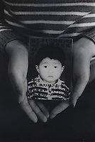 "Mrs Tang, 26, holds a picture of her only son, Chen Zhijie, 5 years and 3 months, who was stolen, she believes by a neighborhood gang. Message read ""My poor son where are you? I miss you very much. Are you okay now? Please come back. Mum can't live without you. Mum dreams of you every night, dreaming that have come back to our sides. Don't know when can our dream comes true.""<br /> Feb 2007<br /> <br /> photo by Richard Jones / Sinopix"