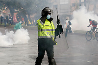 BOGOTA, COLOMBIA - MAY 01 : A police officer moves away of a gas canister used to disperse people taking part in a protest against government and the tax reform during the International Workers' Day on May 01, 2021 in Bogota, Colombia. Hundreds of Colombians protest against a tax bill reform plan for the fourth day in a row which aimed to raise some $ 6.3 billion in additional revenue over 10 years for Colombia, which saw GDP fall 6.8 percent in 2020 .(Photo by Leonardo Munoz/VIEWpress)