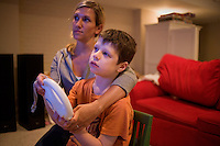Jack Ursitti, age 7, plays Mario Kart on a Nintendo Wii with his teacher Sarah Hoey, of the Nashoba Learning Group, in his home in Dover, Mass., on Monday, July 25, 2011.  Jack has been diagnosed with autism.  After school at his home, Jack works with his teacher and a therapist to do educational and independent leisure activities...Jack Ursitti wears a small GPS ankle bracelet at all times in case he runs off from his family or caretakers. The device will be activated if he goes missing, allowing police and other searchers to find him.
