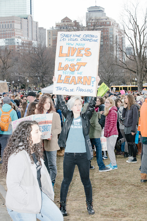 """A woman holds a sign reading """"Sandy Hook. Chicago. Las Vegas. Columbine. / How many lives must be lost before we learn? / The pulse. Parkland."""" as people gather during the March For Our Lives protest and demonstration in Boston Common in Boston, Massachusetts, USA, on Sat., March 24, 2018. The march was held in response to recent school gun violence."""
