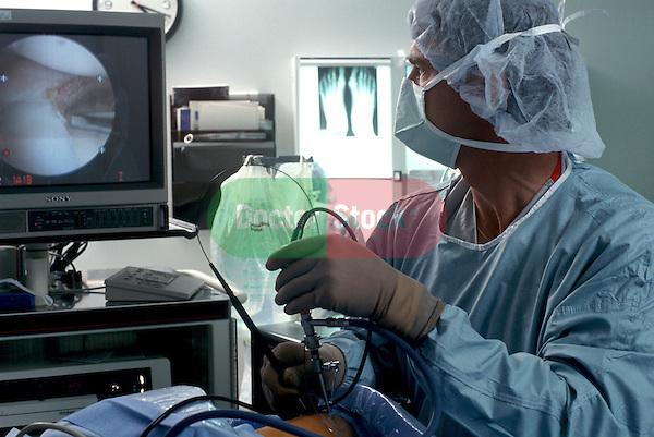 Surgeon repairs knee with arthroscopy