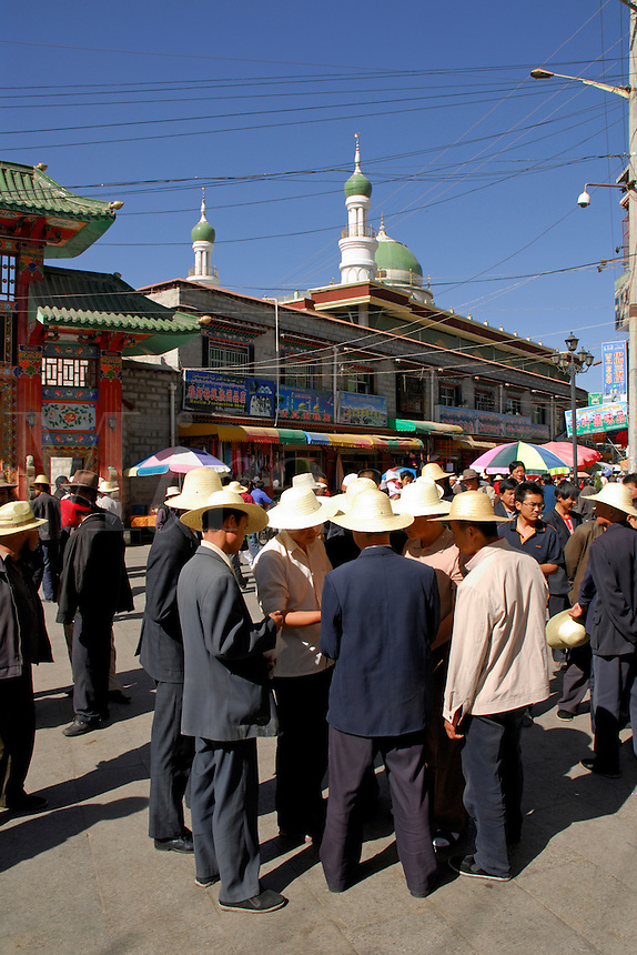 Straw-hatted Tibetan Muslims gather in the marketplace near the mosque, Muslim quarter, Lhasa, Tibet.