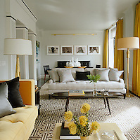 A palette of grey, black and yellow on the walls and soft furnishings unite this chic living/dining room