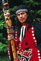 Portrait of a Native Alaskan man in traditional dress and holding an ornately carved and painted walking stick. Alaska.