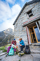 The Via Alta Verzasca is a five day ridge traverse hike above the Valle Verzasca in the Ticino region of Switzerland. Hikers at the Capanna Cognora in the early morning looking at a map of the last day.