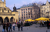 Kracow, Poland; Stare Miasto Old Town city square with yellow sunshades, flower stalls; the Cloth Hall (Sukiennice).