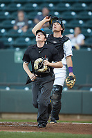 Home plate umpire Austin Jones tracks a fly ball as Winston-Salem Dash catcher Nate Nolan (15) looks on during the game against the Lynchburg Hillcats at BB&T Ballpark on May 1, 2018 in Winston-Salem, North Carolina. The Dash defeated the Hillcats 9-0. (Brian Westerholt/Four Seam Images)