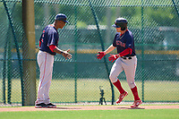 FCL Red Sox coach Jimmy Gonzalez shakes hands with Blaze Jordan (44) as he rounds the bases after hitting a home run during a game against the FCL Pirates Gold on August 2, 2021 at Pirate City in Bradenton, Florida.  (Mike Janes/Four Seam Images)