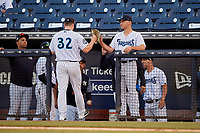Tampa Tarpons starting pitcher Clarke Schmidt (32) high fives Frank German (right) during a Florida State League game against the St. Lucie Mets on April 10, 2019 at George M. Steinbrenner Field in Tampa, Florida.  St. Lucie defeated Tampa 4-3.  (Mike Janes/Four Seam Images)
