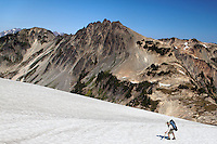 Backpacker climbing snow slope below Pulitzer Peak, Bailey Range Traverse, Olympic Mountains, Washington