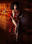 Beautiful naked woman in red kimono lying on the floor in dim dramatic light covering her nude body with an asian fan view from above Image © MaximImages, License at https://www.maximimages.com