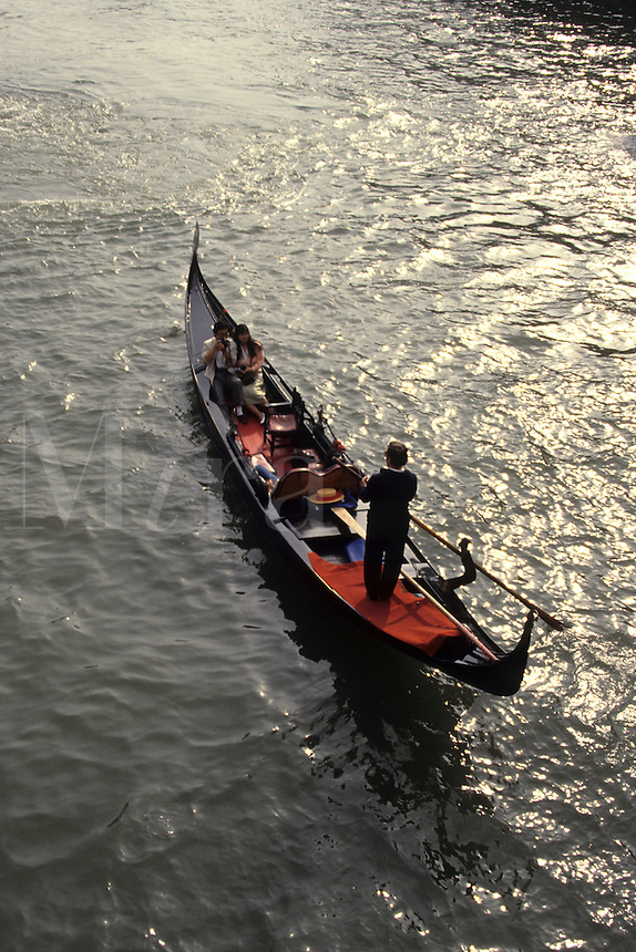 Sunset graphic gondola with tourists into sunset on canal in romantic Venice Ital