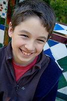 Boy smiling and looking at the camera in the Murillo Gardens, Seville, Andalusia, Spain.
