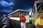 Joe Kowalski (center) checks the darkening cloudsd during a horse race at the Yonkers Raceway in Yonkers, New York on Tuesday, May 29, 2012. (Photograph by Yana Paskova for The New York Times)