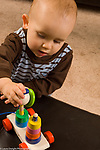 13 month old toddler boy playing with toy with stacking shapes and spindle