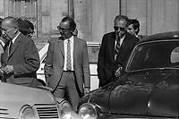 """Place Anatole France. 19 septembre 1971. Scène de reconstitution judiciaire : au 1er plan 2 voitures (une """"Juva 4"""" à gauche et une Frégate noire à droite), dans la voiture noire un agent refait le geste du meurtrier, bras tendu tenant une arme à feu ; en arrière-plan un groupe d'homme discutent (policiers, juge d'instruction...). Cliché pris lors de la reconstitution, 13 ans après, du meurtre de Maurice Cathala (membre de la Convention républicaine) dans la nuit du 26 septembre 1958 par un groupe de militants communistes (assassin présumé Louis Richon photographe de presse au quotidien """"Le Patriote"""")"""