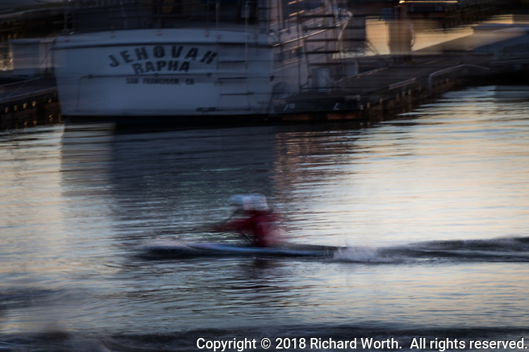 An enthusiastic kayaker, captured in slow shutter blur, passing the moored Jehovah Rapha:  God Who Heals.  San Leandro Marina on San Francisco Bay.