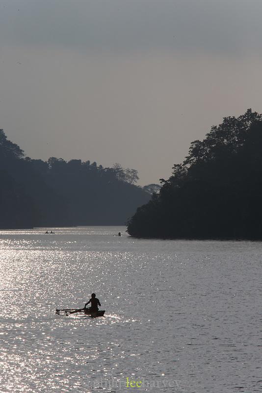 Child canoeing across the Fjord at sunrise, Tufi, Cape Nelson, Oro Province, Papua New Guinea
