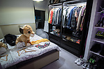 """© Joel Goodman - 07973 332324 - all rights reserved . 12/01/2020 . Salford , UK . Second bedroom of the rented flat of Kayne Lewis (25) , which he uses as a changing room and which he shares with Chase (the 5 month old Chihuahua) and some fish , in apartment block """"Duet"""" , on Salford Quays in Greater Manchester . Photo credit : Joel Goodman"""