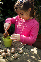 Young girl (seven year old) planting spring bulbs